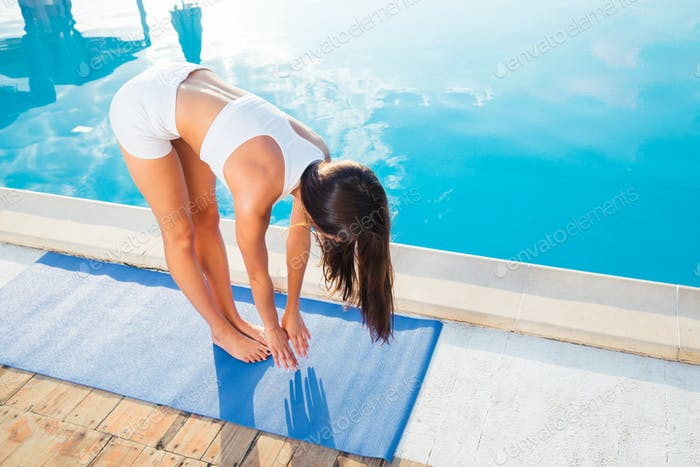 Woman doing yoga exercises on mat