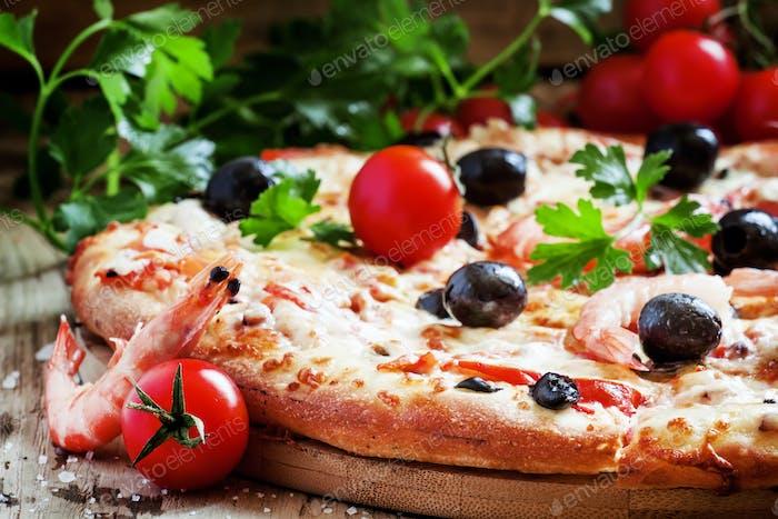 Pizza mit Meeresfrüchten und schwarzen Oliven