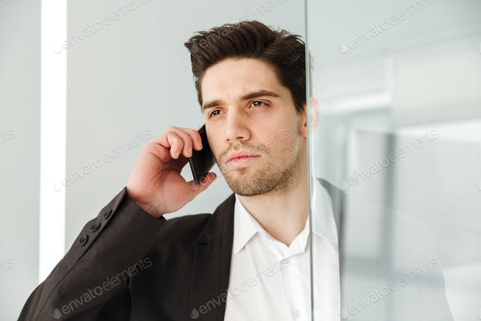 Serious young businessman talking by phone.