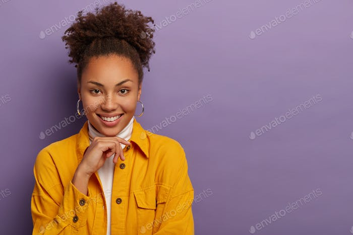Charming beautiful young woman smiles sincerely, dressed in yellow shirt, keeps hand under chin, has