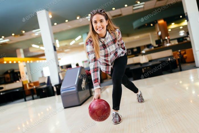 Fokussierte glückliche Frau genießen Bowling
