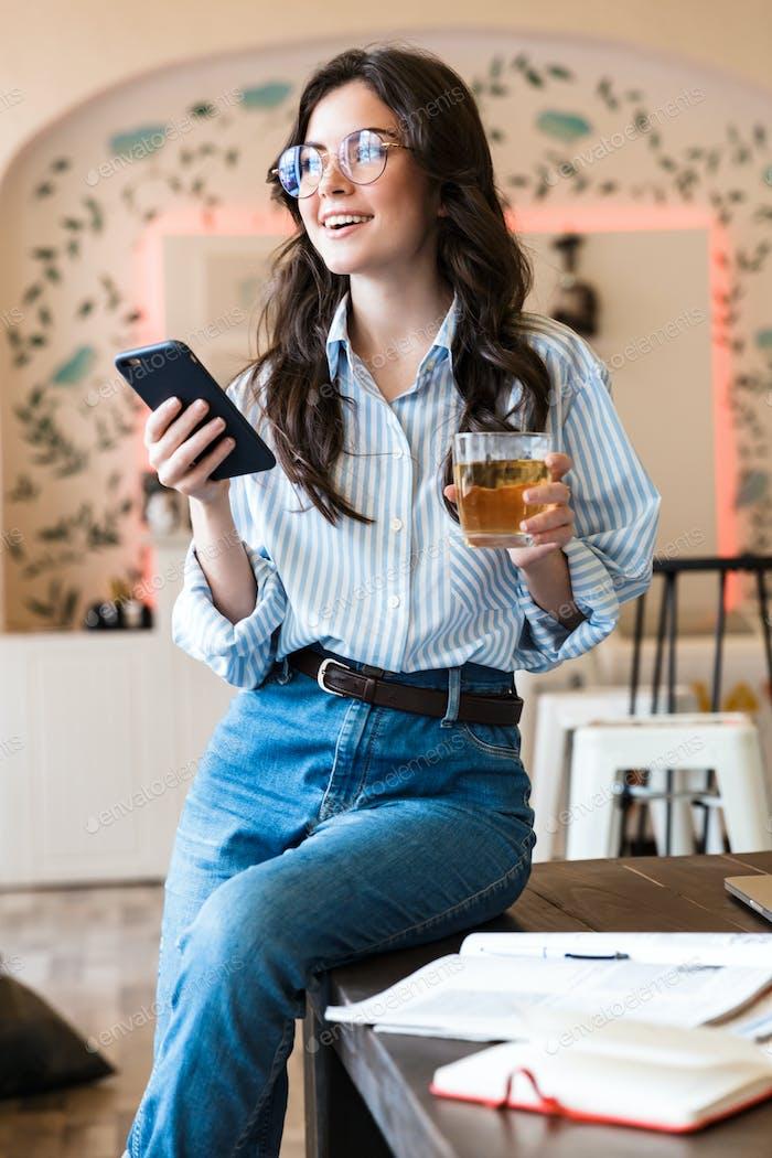 Attraktive junge Brünette Frau, die im Café drinnen studiert