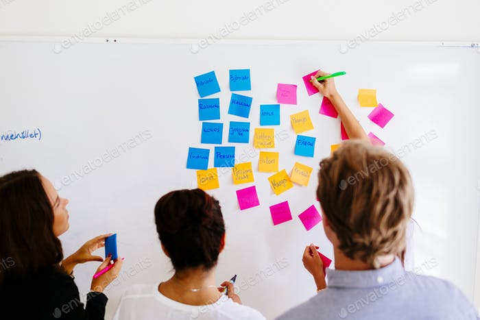 Business people fixing sticky notes at office