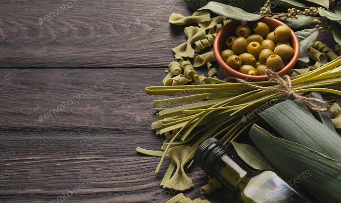 Assorted italian green pasta on wooden background