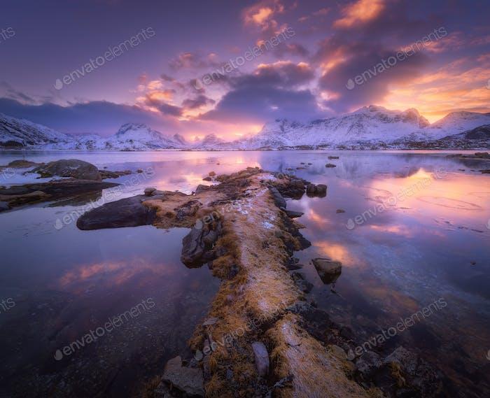 Seeküste, verschneite Berge und traumhaft violetter Himmel bei Sunet