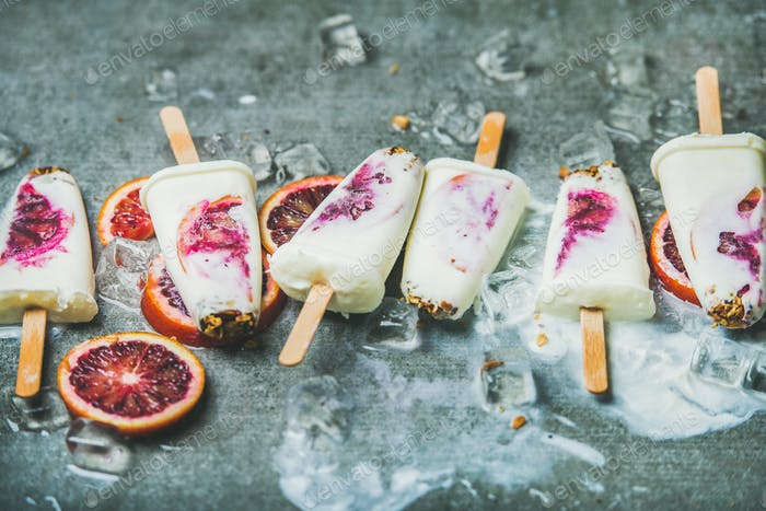 Red orange, yogurt, granola popsicles on ice cubes, healthy dessert