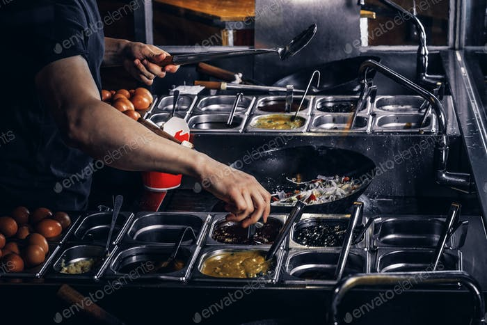 Cooking process in an Asian restaurant. Cook is fry vegetables with spices and sauce in a wok