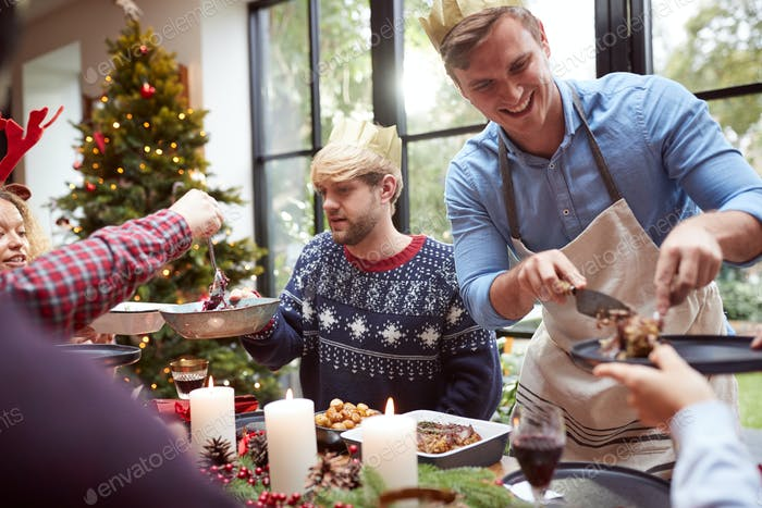 Group Of Friends Sitting Around Dining Table At Home As Vegetarian Christmas Dinner Is Served