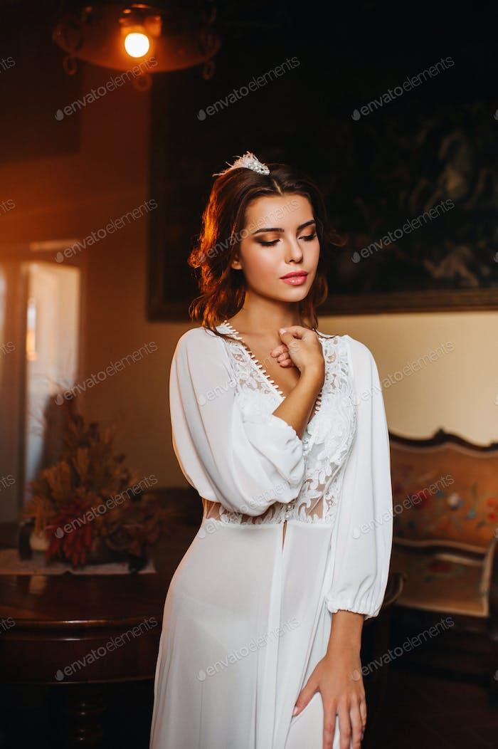eine Braut in Unterwäsche und eine weiße Robe im Inneren einer Villa in Italien bei einer Hochzeit.Morgen