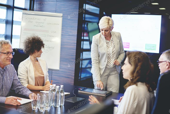Mature woman doing presentation with digital tablet