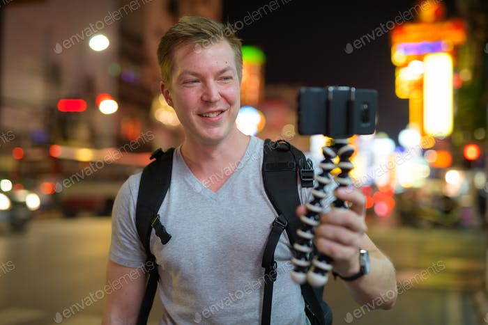 Young happy tourist man vlogging in the streets of Chinatown at night