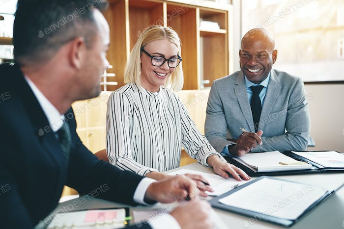 Diverse group of businesspeople laughing during an office meeting
