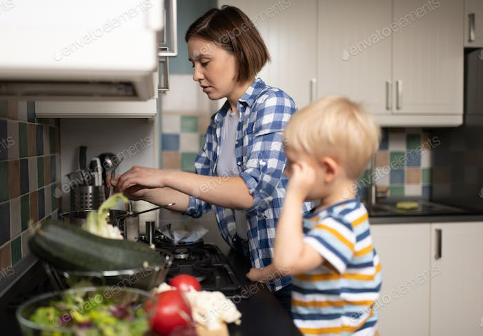 Female babysitter making dish with little boy at kitchen at home