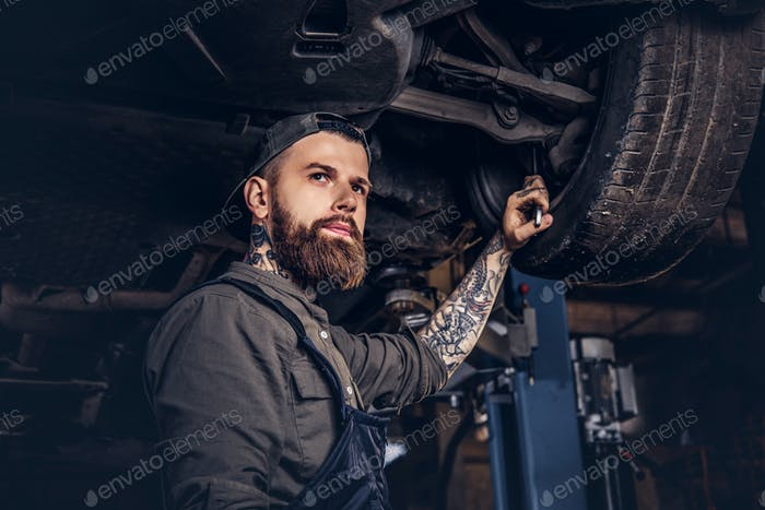 Two bearded auto mechanic working in repair garage.