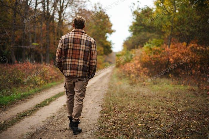Masculine caucasian man strolling in autumn forest