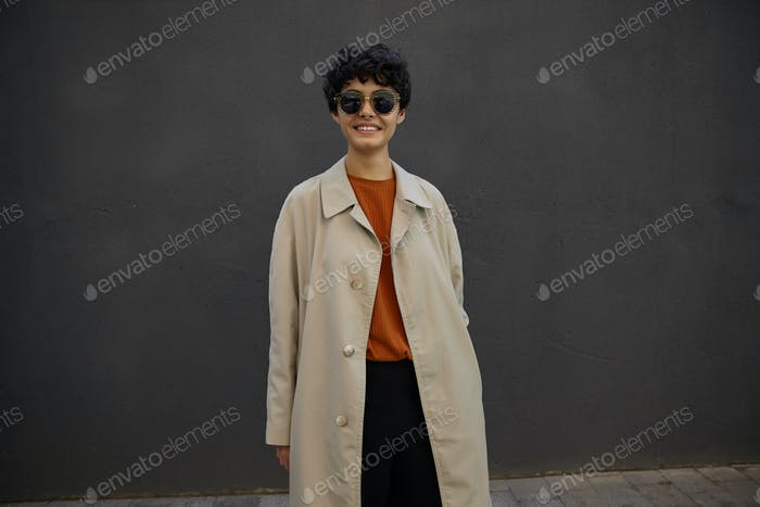 Pretty stylish young curly brunette female with short haircut looking at camera positively