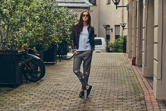 Beautiful fashionable brunette in a stylish clothing and sunglas