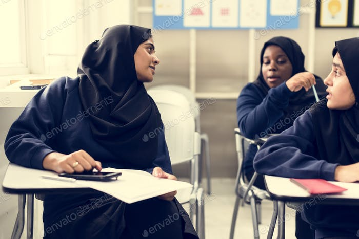 diverse muslim girls studying in classroom