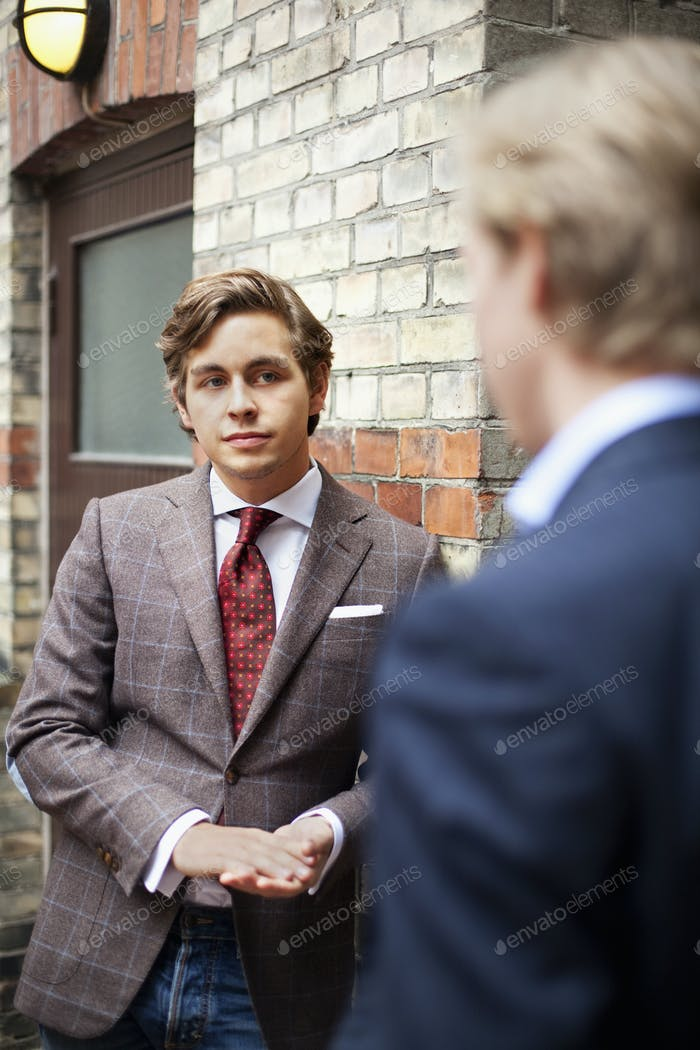 Confident businessman standing with partner by building