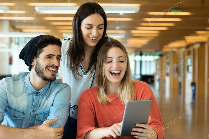 Studenten mit digitalem Tablet in der Universitätsbibliothek.