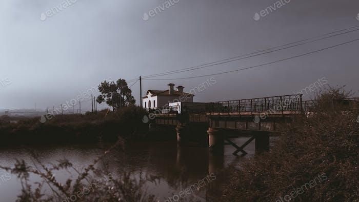 Abandoned house, river, and bridge