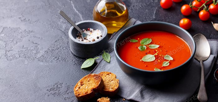 Tomato Soup with Basil in a Bowl. Grey Background. Copy Space.