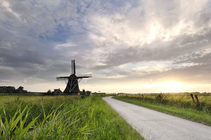 road by Dutch windmill at sunset in farmland