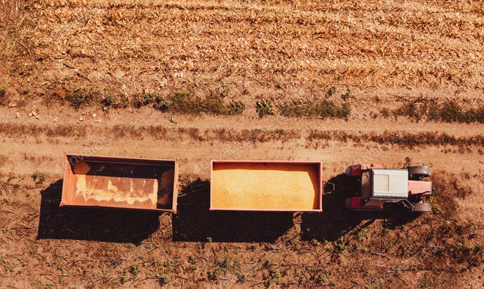 Aerial view of agricultural tractor with cargo carts in field