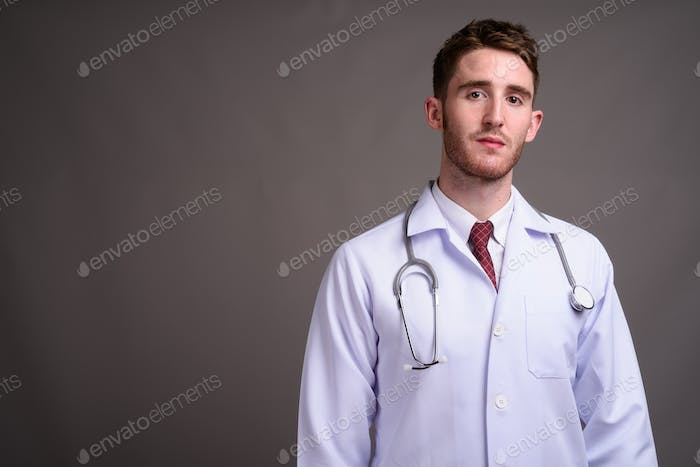 Young handsome man doctor against gray background