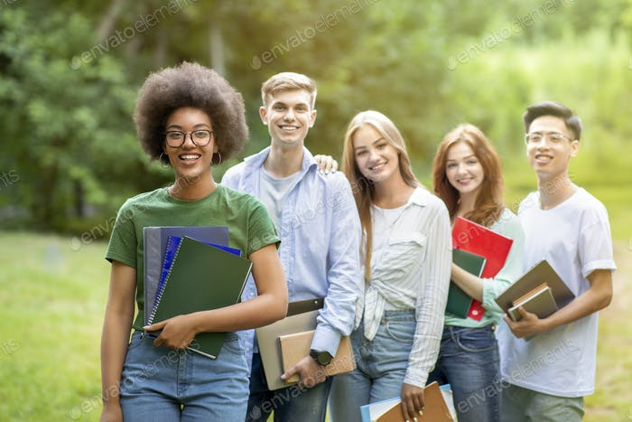Group of young happy multiethnic students posing together outdoors at university campus