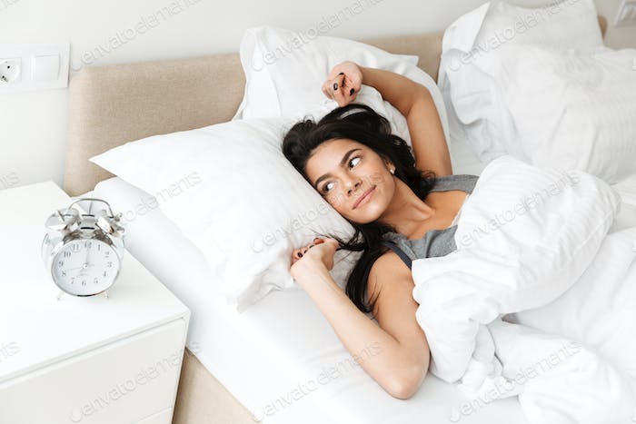 Portrait of pleased relaxed woman stretching in bed at bedroom w