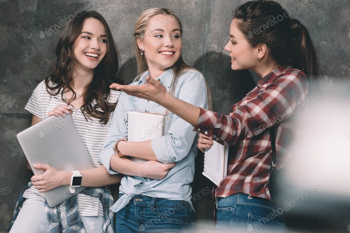 Three attractive students with copybooks and laptop standing at wall