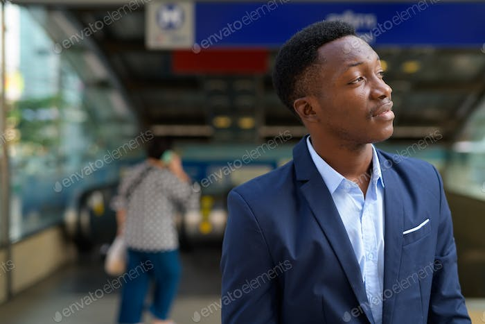 Profile view of young handsome African businessman thinking outside the subway train station