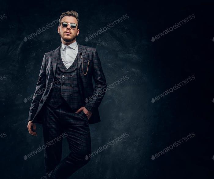 Стильный молодой человек, одетый в элегантный костюм с солнцезащитными очками, позируя рукой в кармане