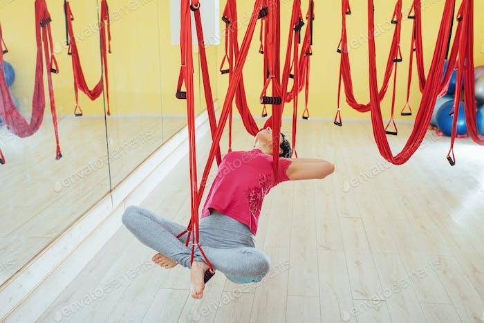Junge schöne Frau üben Yoga Fliegen Sie mit einer Hängematte im Studio.