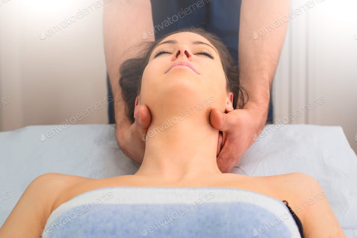 Therapist massaging the neck of woman In the by a professional