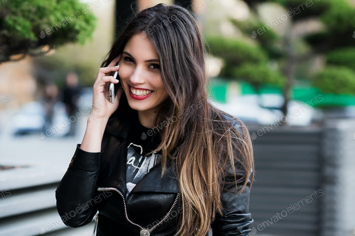 Portrait of smiling beautiful young woman close up with mobile phone, against background summer