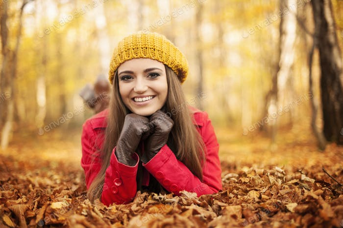Smiling woman lying down on autumn leaves
