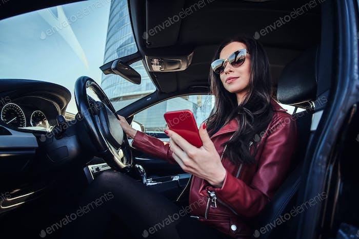 Junge hübsche Frau sitzt in ihrem Auto, während sie auf dem Handy chatten