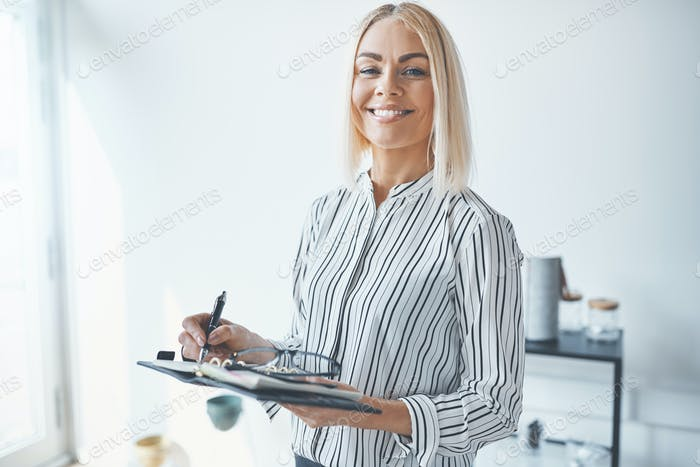 Smiling young businesswoman writing notes while working in an office