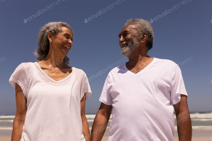Low angle view of happy senior couple holding hands and looking each other on beach in the sunshine