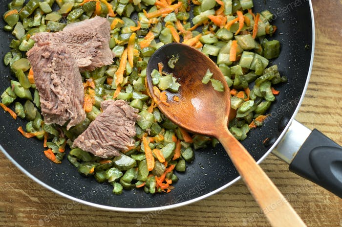 Flat lay view Frying pan with beef carrot and greens