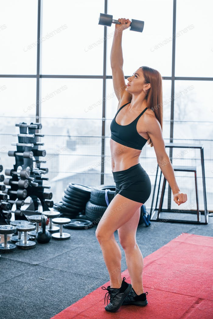 Женщина в черной спортивной одежде имеют упражнения с гантелями в тренажерном зале