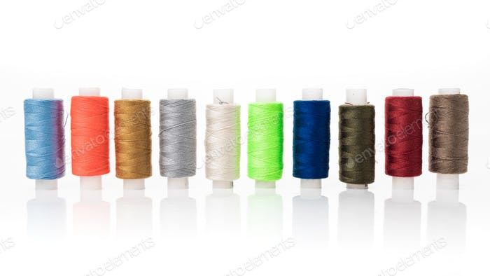 tailor needles and threads over white background