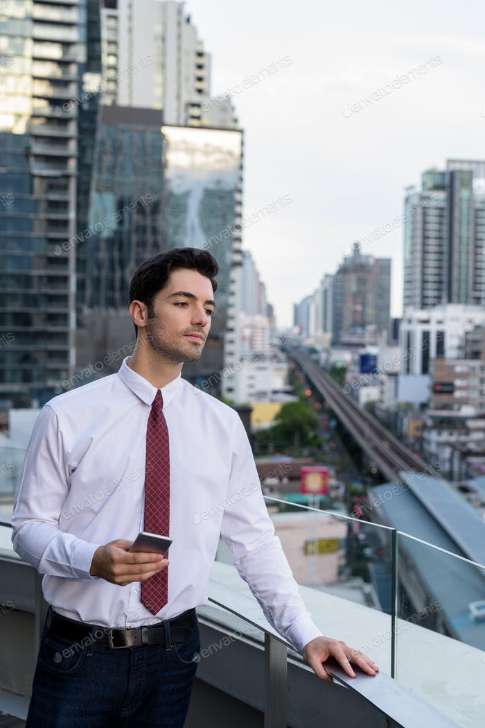 Portrait of young handsome businessman in city