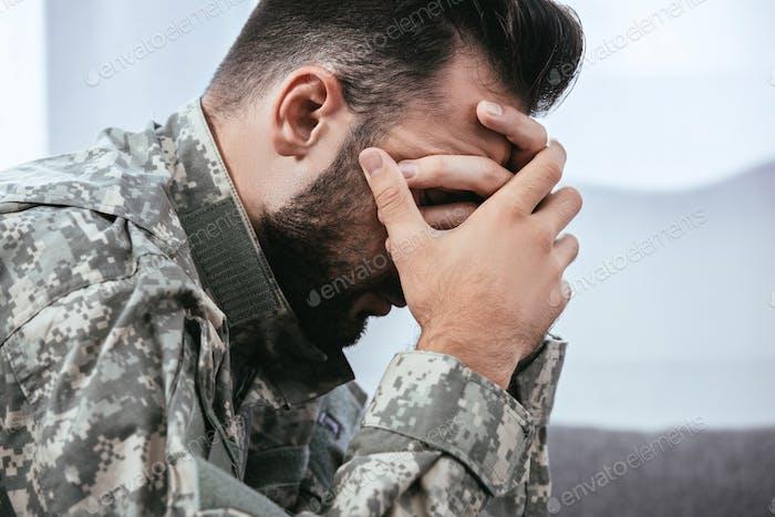 Seitenansicht eines depressiven Armeemannes in Militäruniform mit posttraumatischer Belastungsstörung
