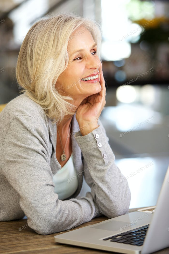 attractive older woman smiling by laptop with head in hand