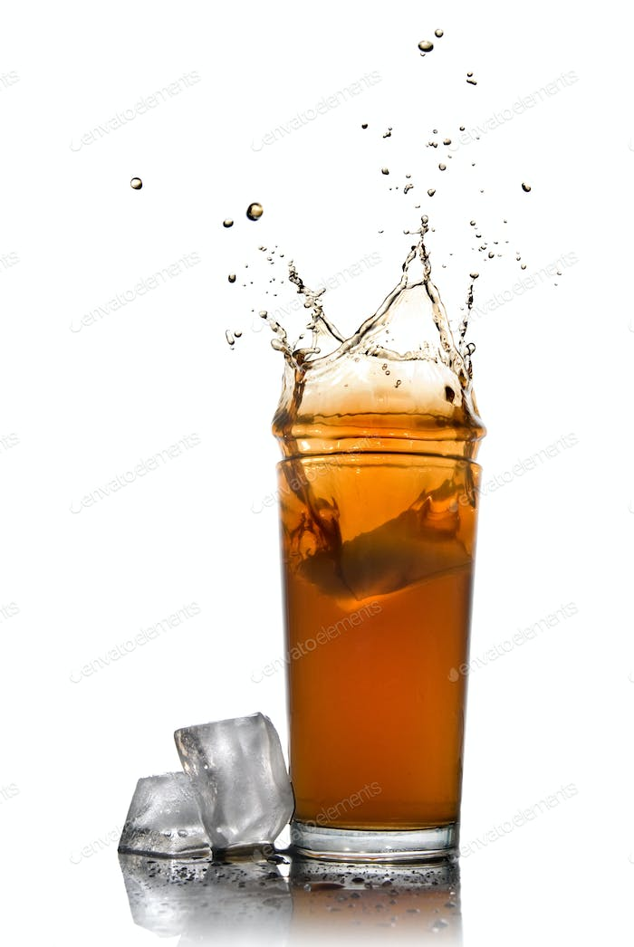 Beautiful splash of cola in glass and ice cubes isolated on whit
