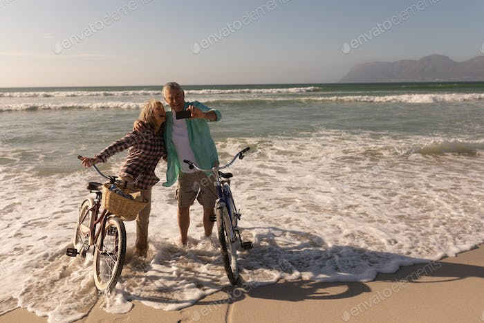front view of active senior couple taking selfie with mobile phone on the beach