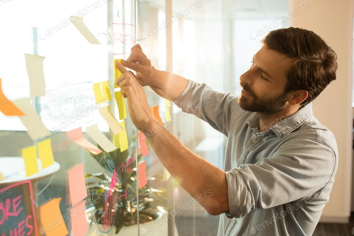 Young businessman sticking adhesive notes on glass